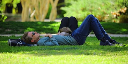 guy lying on the grass using Thich Nhat Hanh mindfulness techniques