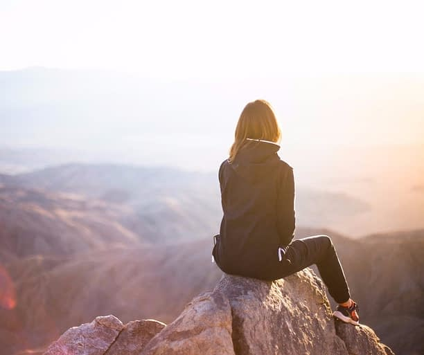 Woman sitting on top of mountain. If you want to change your life, you can.